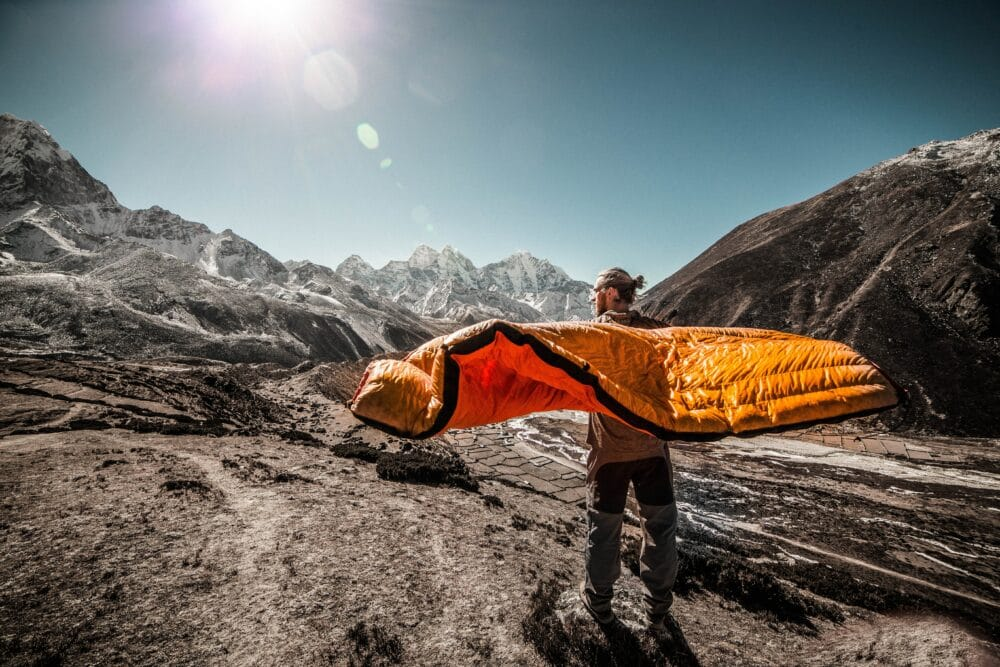 A man opening a sleeping bag at the base of a mountain
