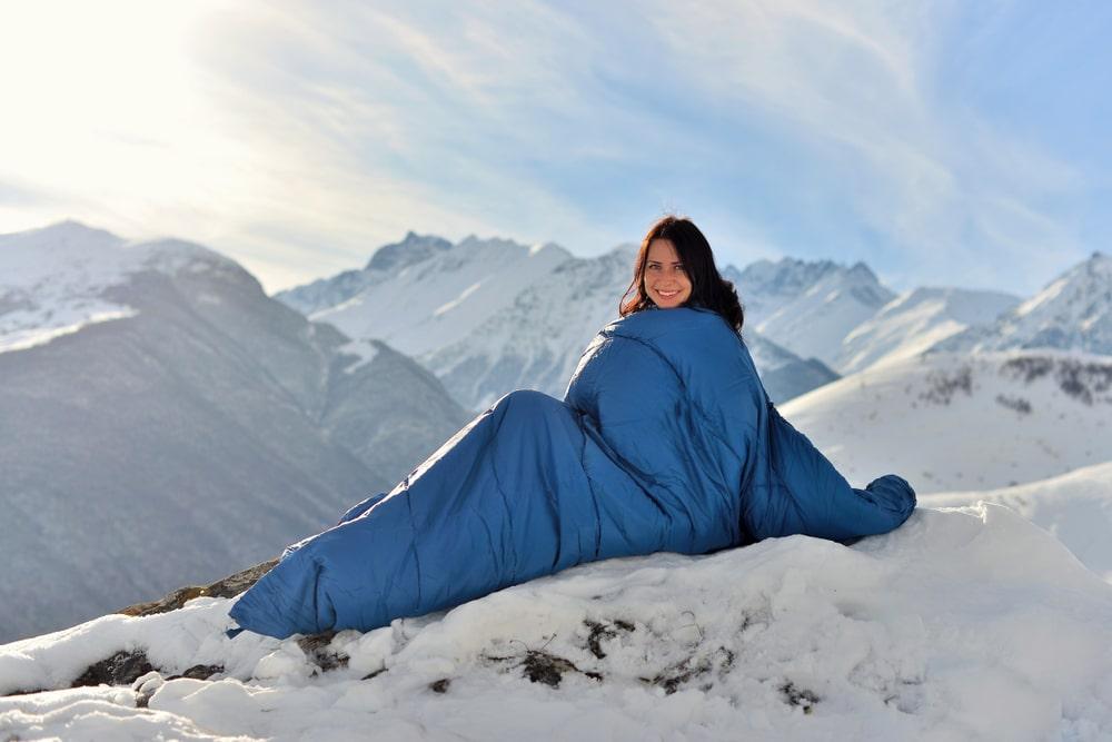 Happy woman in sleeping bag in snowy mountains in winter.