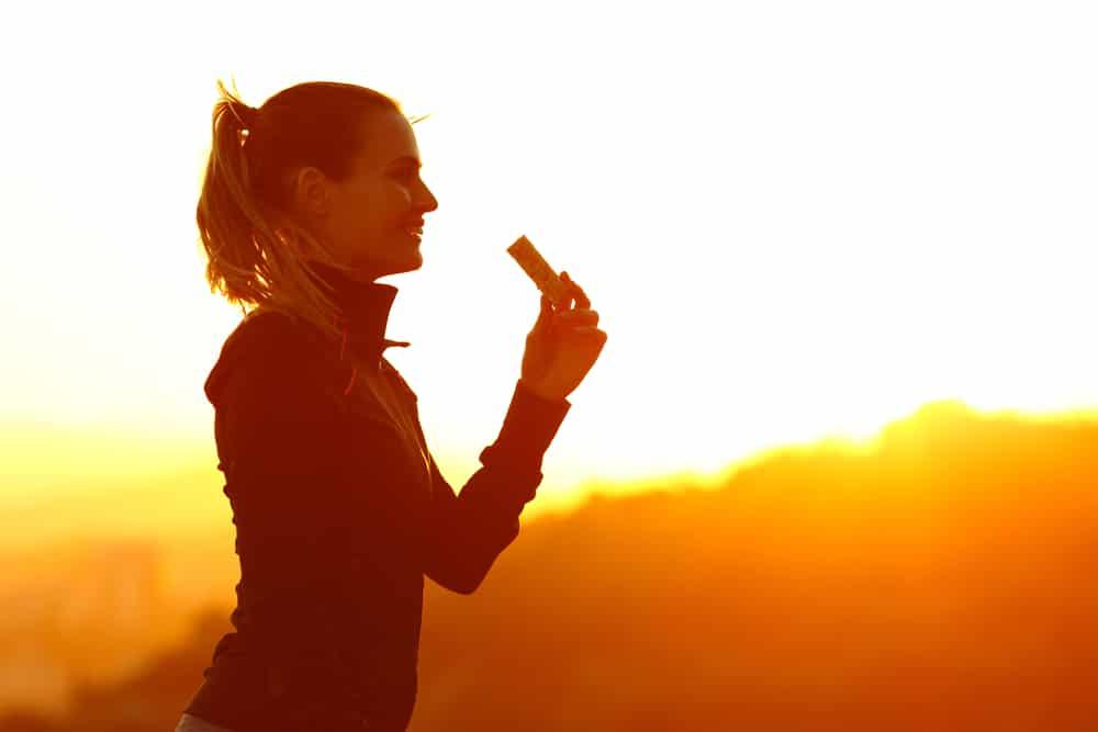Silhouette of runner woman eating energy bar
