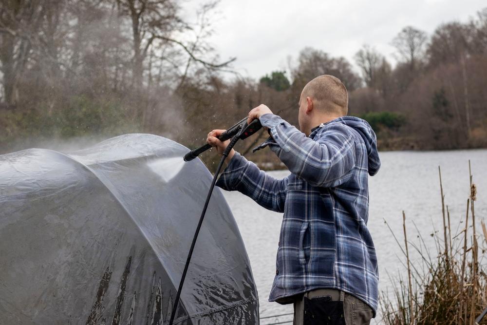 Man jet washing his fishing bivvy