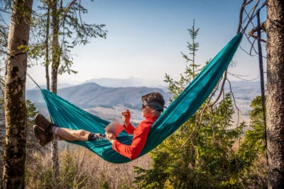 Young happy man relaxing lying in hammock on top of mountain