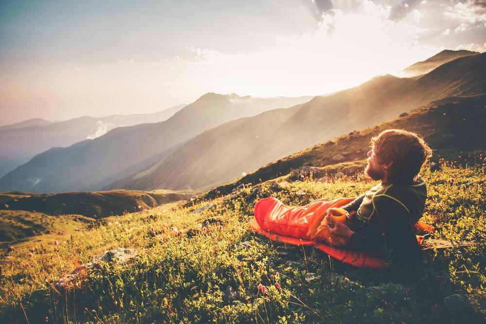 Man relaxing in sleeping bag enjoying sunset mountains landscape
