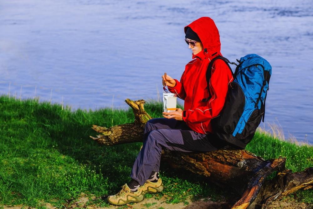 Backpacker eating freeze dried food