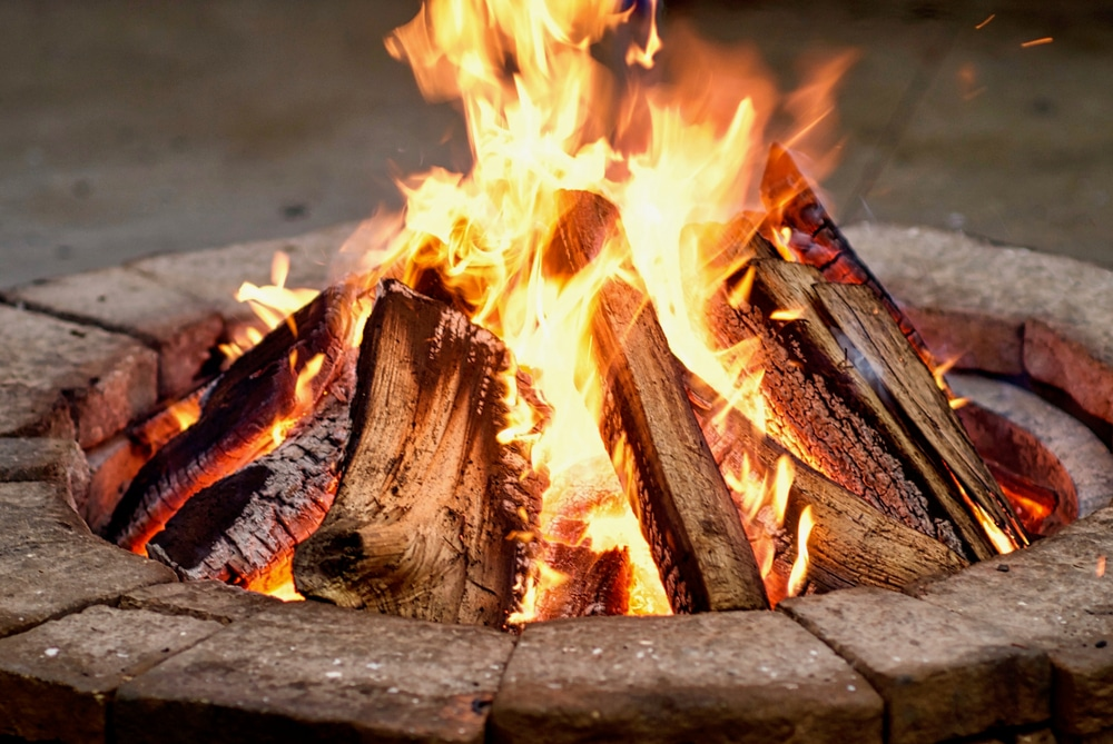 roaring fire with blurred flames from wood logs in a stone firepit