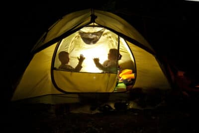 two kids in a camp tent at night