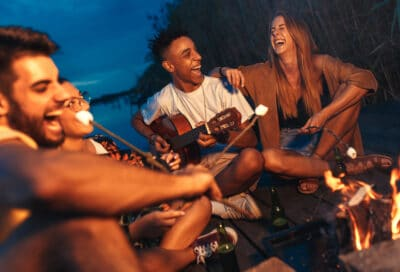 a group of friends laughing around a camp fire.