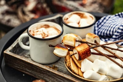 two cup of cocoa or hot chocolate and skewers of roasted marshmallows over campfire