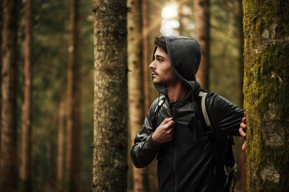 man wearing a hoody and walking in a forest