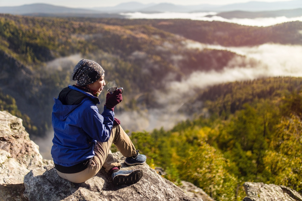 young woman is sitting with a mug of tea on a cliff overlooking the autumn mountains with fog