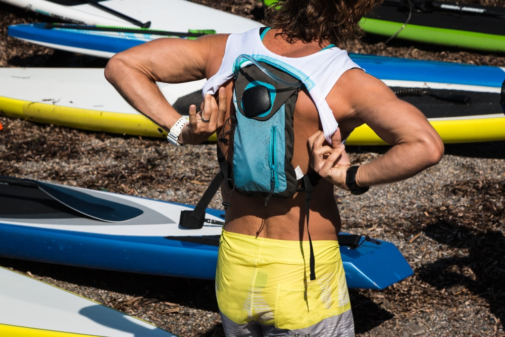 Boy with Hydration Pack on His Shoulder Wearing White Shirt before Surfing,