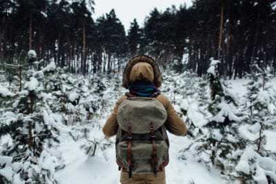 Woman in winter warm jacket with fur and rucksack walking in snowy winter pine forest