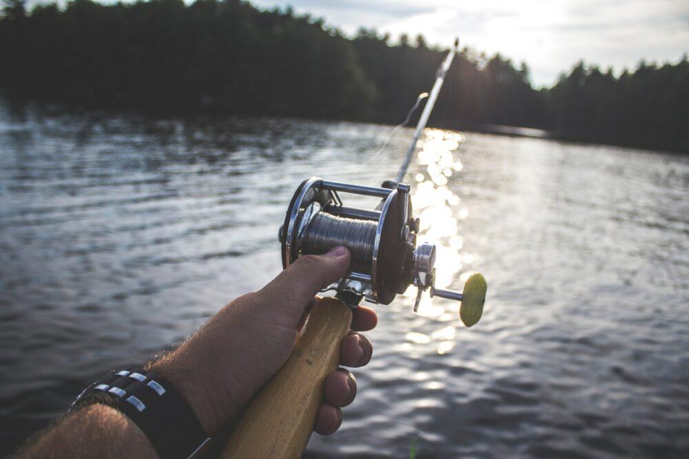 man holding fishing rod over lake