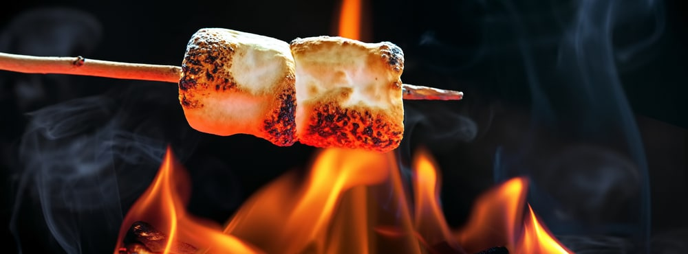 Two marshmallows roasting over fire flames.