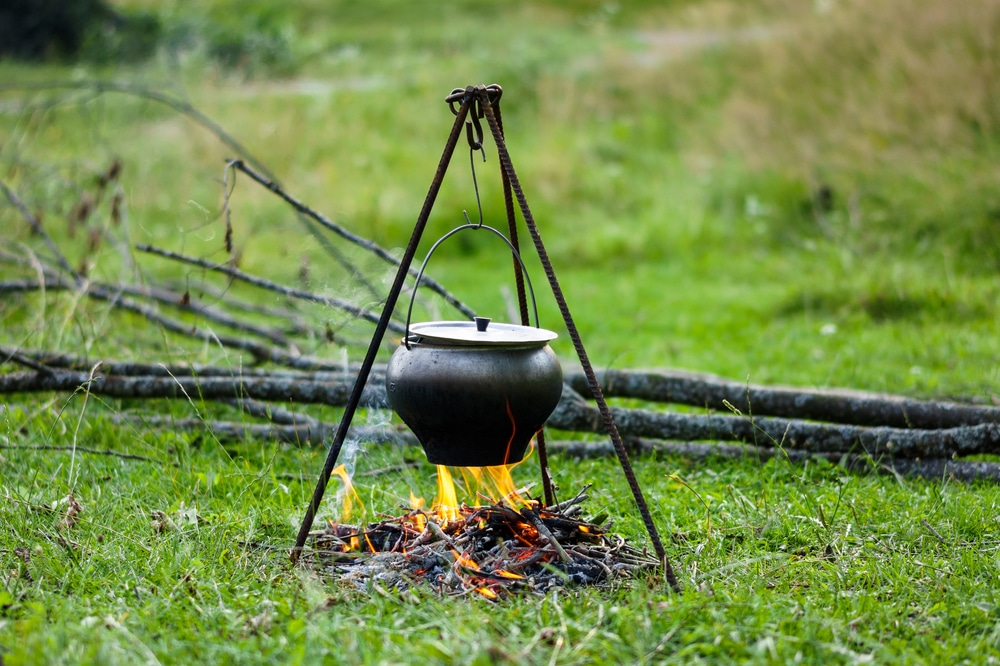 Cooking in cauldron from cast iron on the tripod over the open fire.