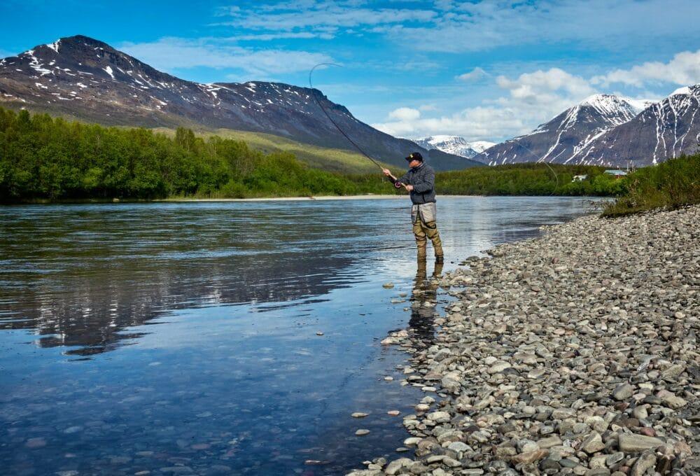 a man with a fishing rod at a lake