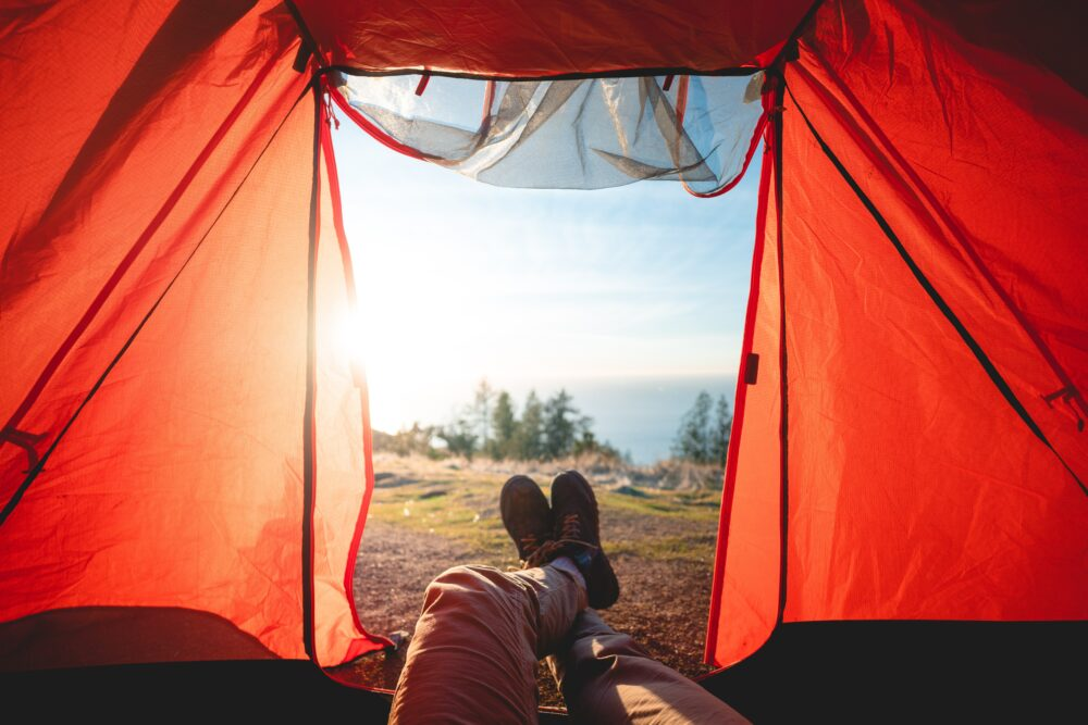 man relaxing in camping tent