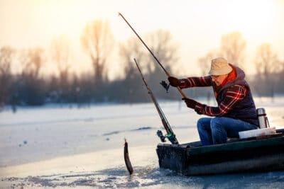 Happy elderly fisherman catch fish on the frozen river in winter