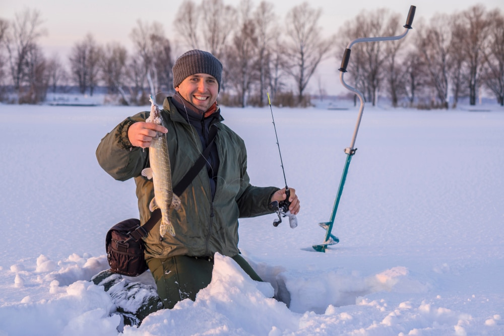 Fisherman in action with trophy in hand. Catching pike fish from snowy ice at lake.