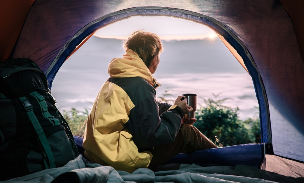 young tourist man holding coffee cup in the tent in morning enjoying the leisure and freedom.