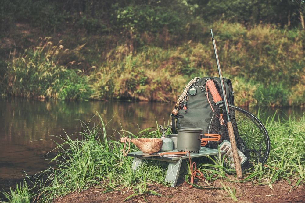 Backpack and fishing rod on the river.
