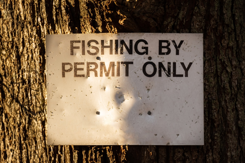 Close up of a fishing by permit only sign attached to a large tree in the winter sun