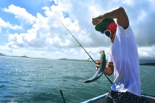 a man fishing with a fishing rod on a boat