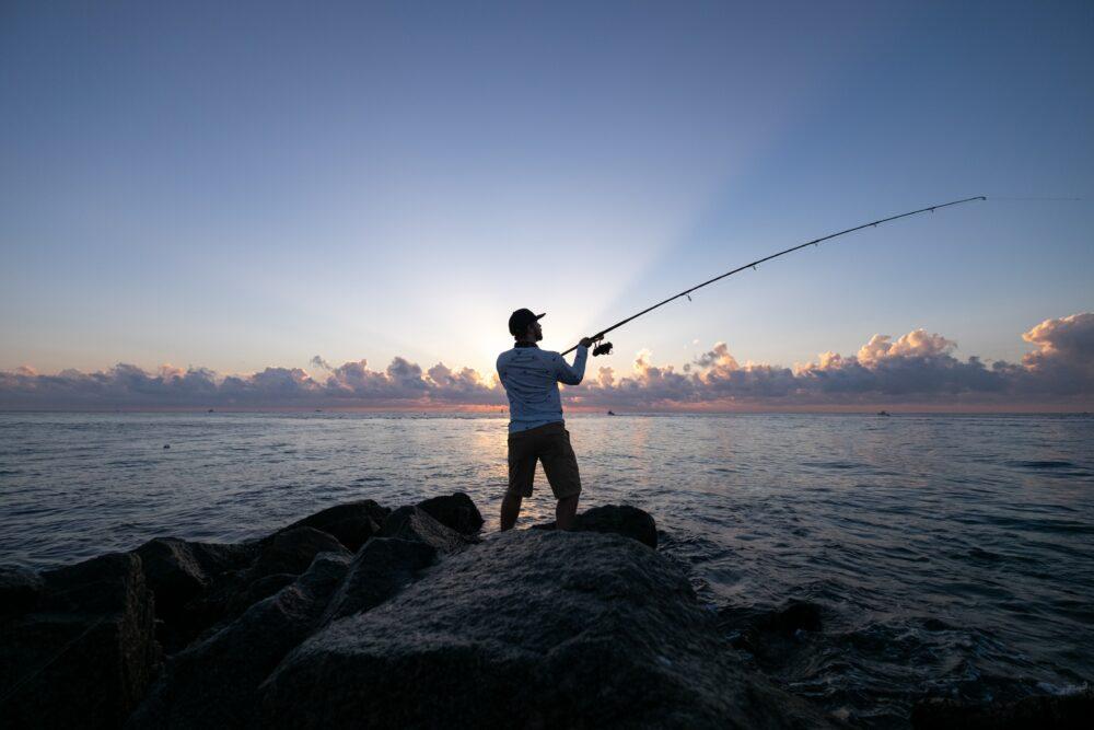 Man fishing on jetty at dawn.