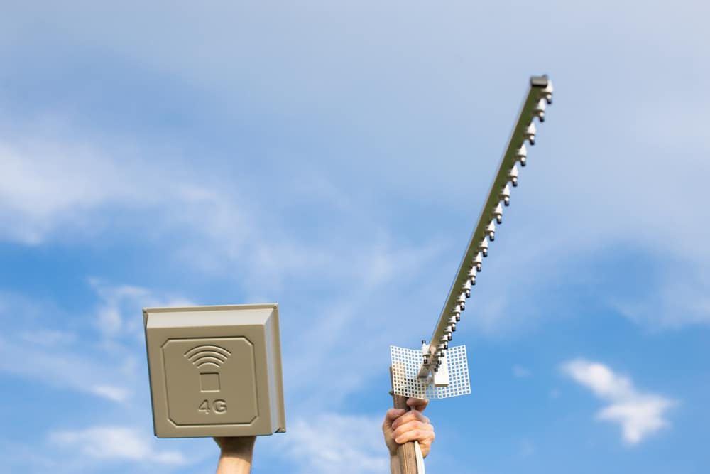Hands holding two different antennas for mobile internet 4G and 5G, to improve coverage, with blue sky background.